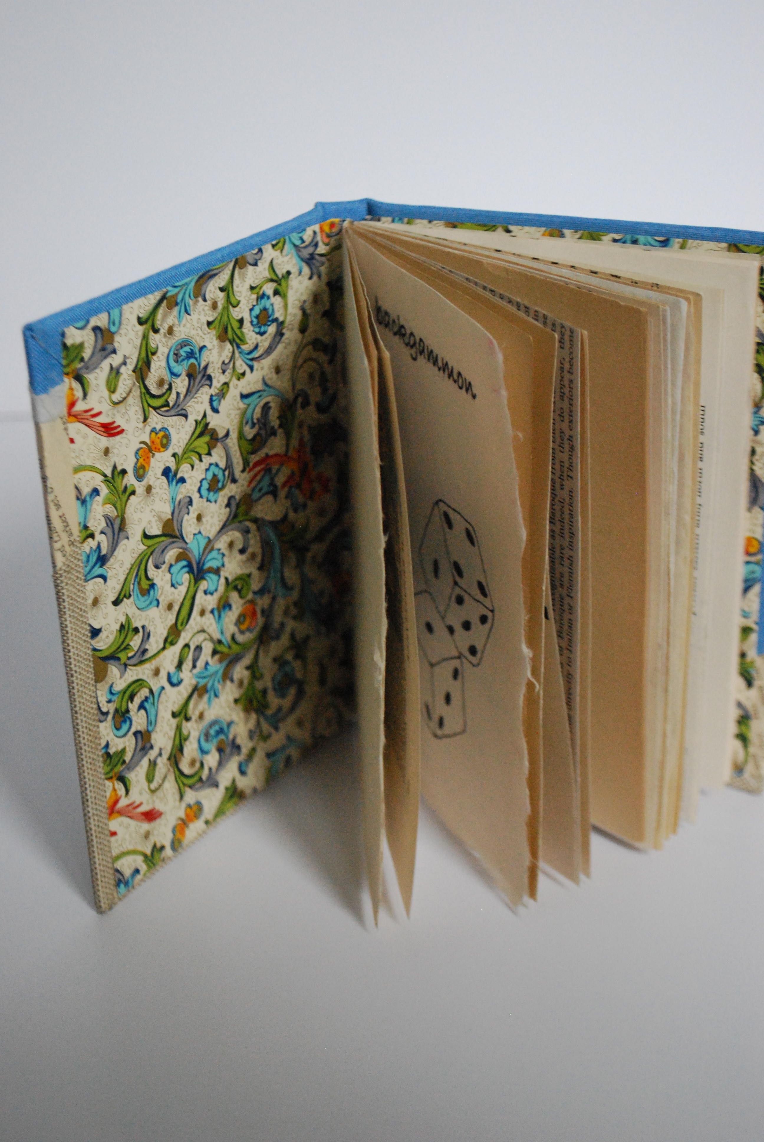 Book propped open showing decorative end papers and mixed paper pages