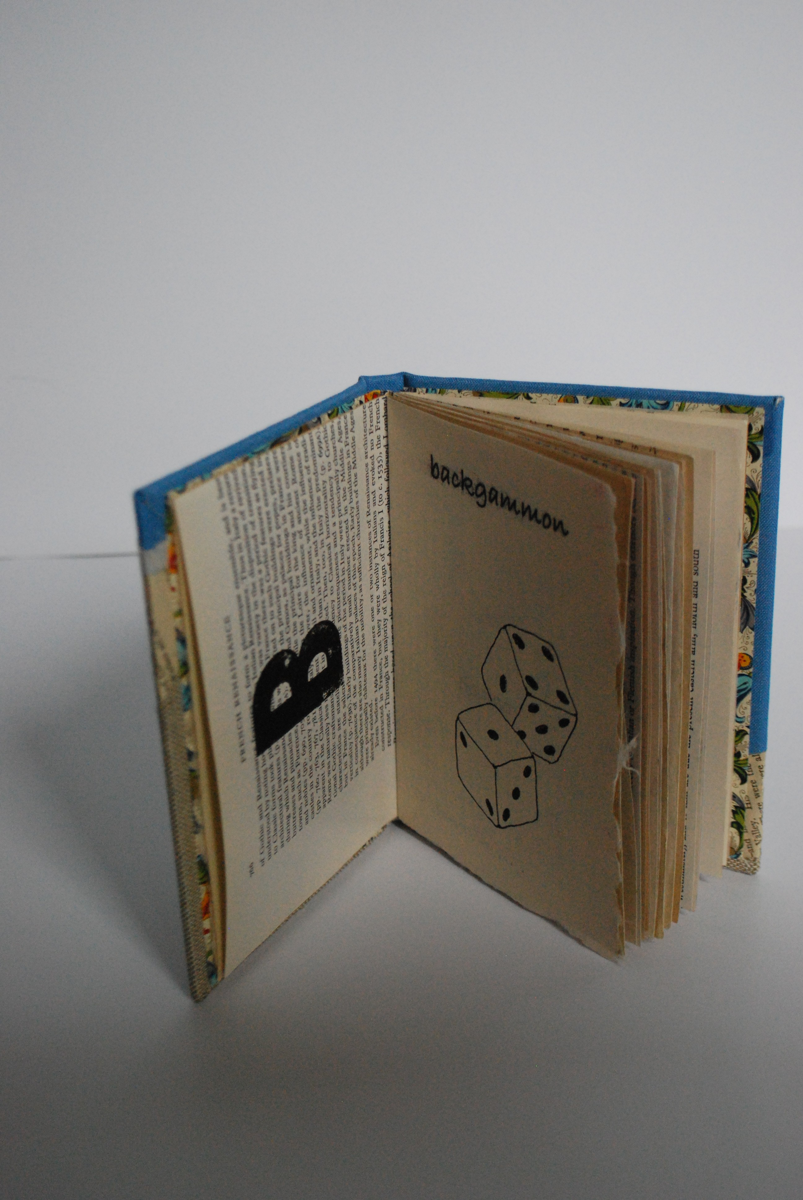 """Book opened to """"B"""" showing dice image and text """"backgammon"""""""