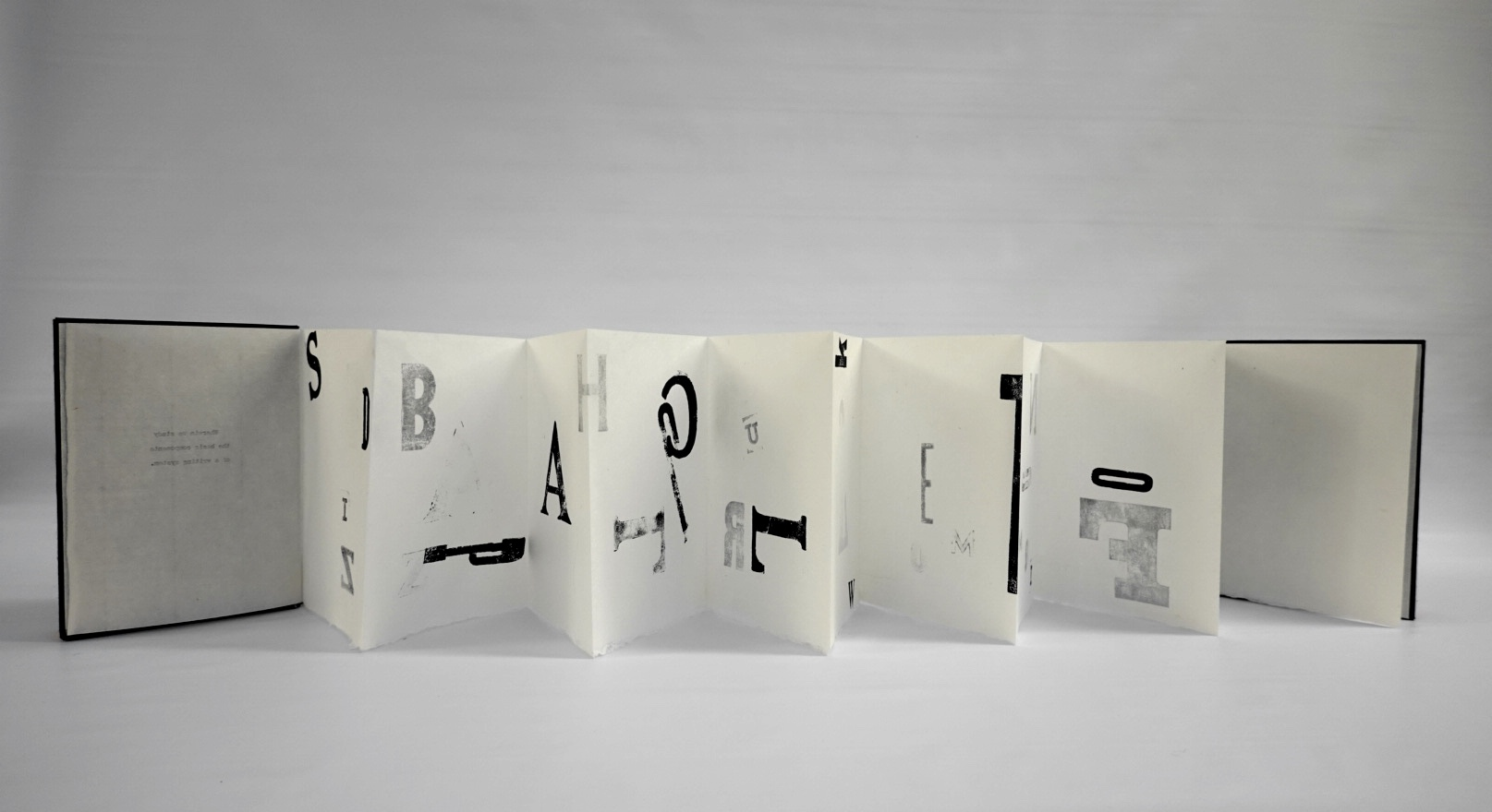 An accordion abecedarian book using Goyu paper with hand stamped reclaimed mismatched wood type and black book cloth on the covers.